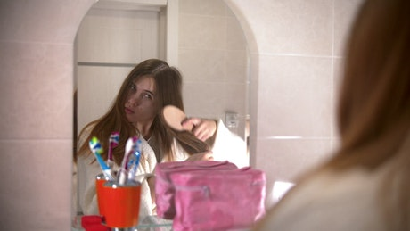 Young woman brushing her hair in the mirror