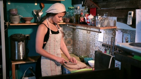 Young woman chopping in the kitchen
