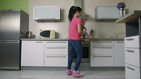 Young woman cooking in a kitchen carrying her baby