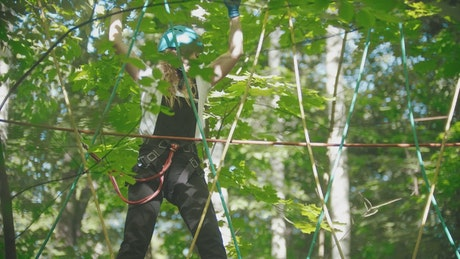 Young woman crossing the ropes in the woods