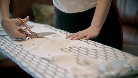 Young woman cutting white fabric with scissors