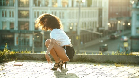 Young woman dancing on the roof of a building