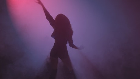 Young woman dancing under a cloud of smoke and a purple light