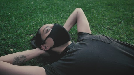 Young woman doing sit-ups with a face mask