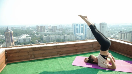 Young woman doing yoga exercises on a rooftop
