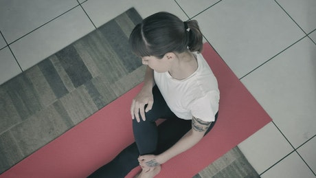 Young woman doing yoga on a red mat
