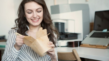 Young woman eating takeout food on office break