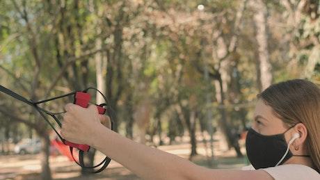 Young woman exercising at park using face mask