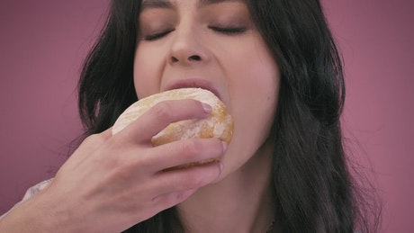 Young woman giving a big bite a donut
