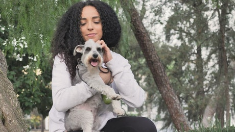Young woman in a park carrying her schnauzer dog