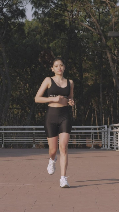 Young woman jogging head-on outdoors