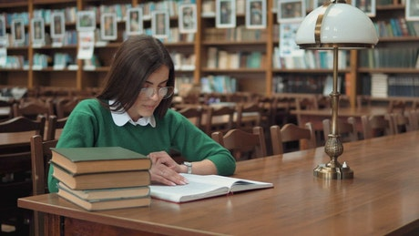Young woman learning in library smiles at camera