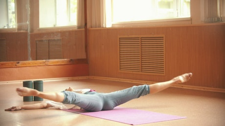 Young woman lying on the floor doing yoga