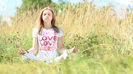 Young woman meditating in a field