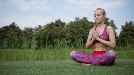 Young woman meditating in prayer pose in nature