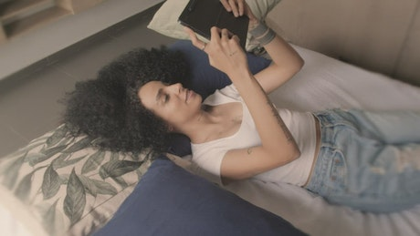 Young woman on a video call lying on a bed