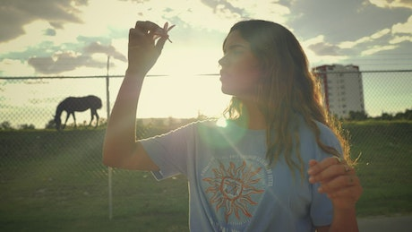 Young woman placing a flower on her ear in a sunset