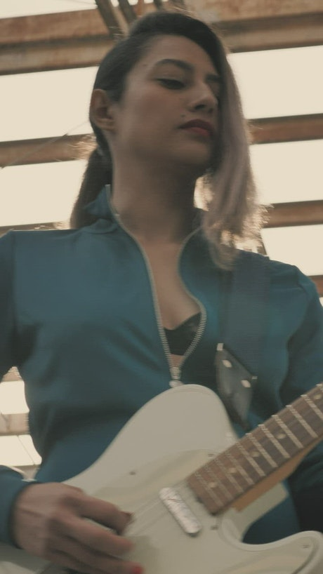 Young woman playing a white electric guitar