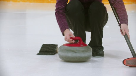 Young woman playing curling on an ice rink