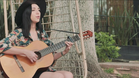 Young woman playing guitar and singing in a garden