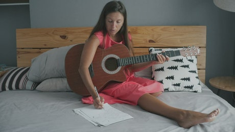 Young woman playing the guitar on the bed