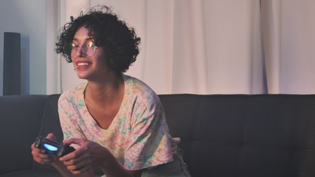Young woman playing video games on the sofa