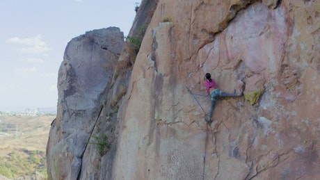 Young woman practicing extreme mountaineering on a mountain
