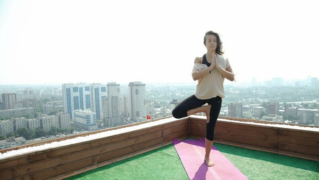 Young woman practicing yoga in the rooftop