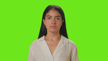 Young woman putting on a mask on a green background