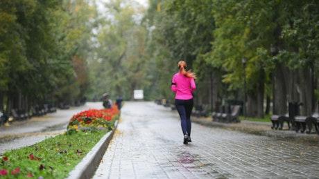 Young woman running through an empty park