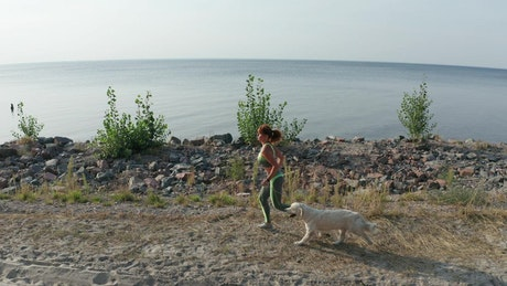 Young woman running with her dog near a coast