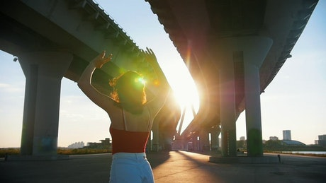 Young woman skating below a bridge in the sunlight