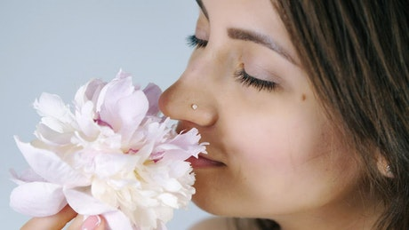 Young woman smelling a white flower