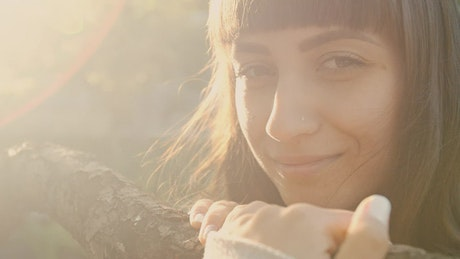 Young woman smiling next to a branch