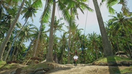 Young woman swings between palm trees at Bali resort