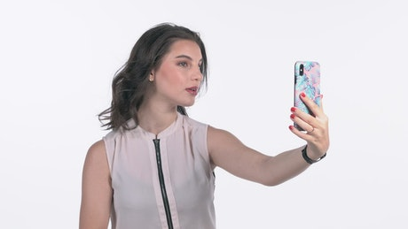 Young woman takes selfies with a smartphone