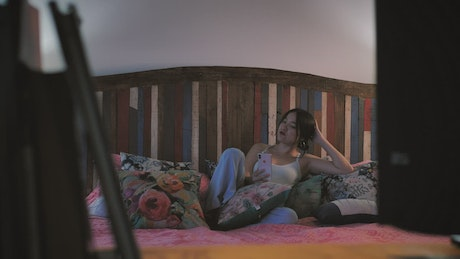 Young woman talking on video call lying on her bed