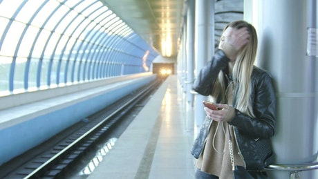 Young woman texting on her mobile phone at the metro station