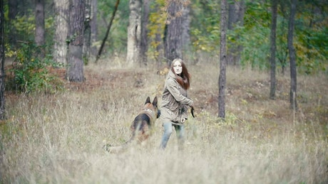 Young woman throwing a stick away at her dog