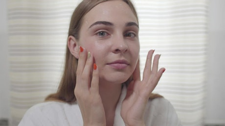 Young woman treats acne with skincare routine