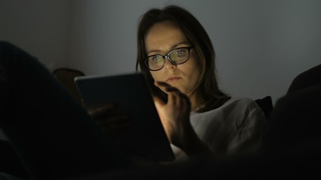 Young woman using a tablet in a dark room