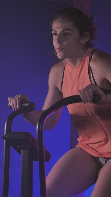 Young woman using an air bike in her workout