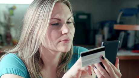 Young woman using the phone with credit card
