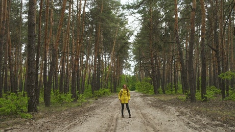 Young woman walking in the forest dirt path