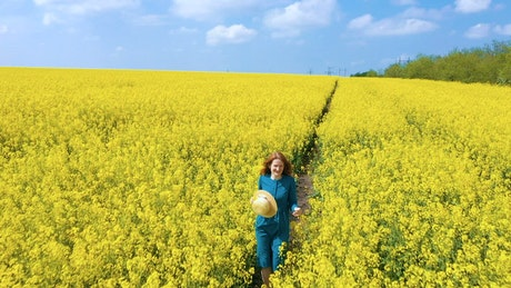 Young woman walking through rapeseed field