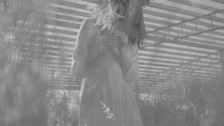 Young woman wearing a wreath collecting wild flowers