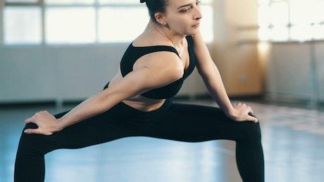 Young woman wearing sportswear doing warm-ups