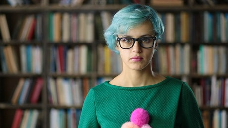 Young woman with glasses in a library, portrait