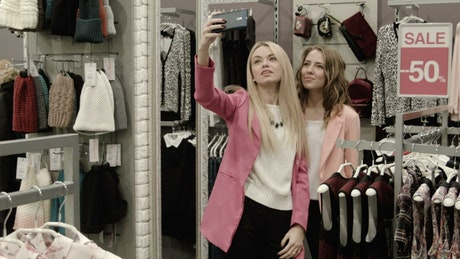 Young women doing selfie in a clothing store