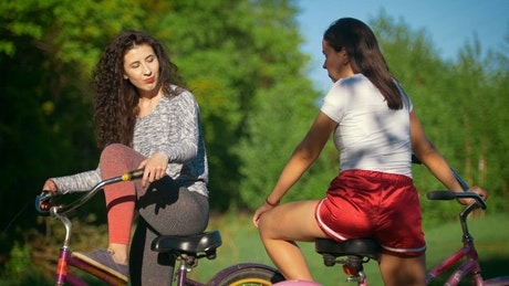 Young women in bikes talking in the park